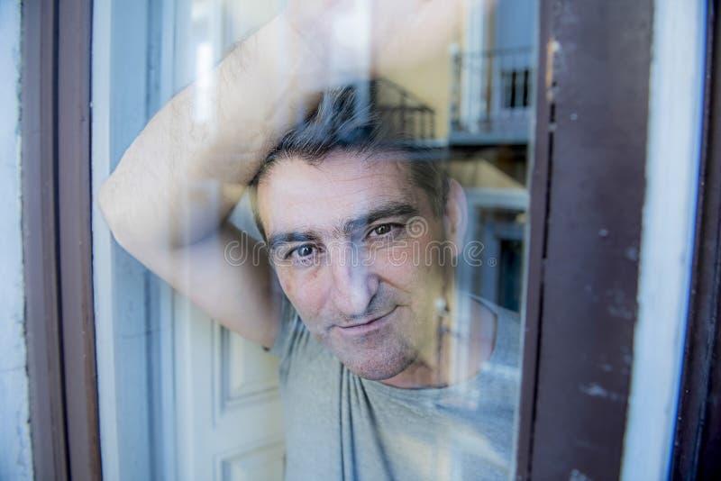 Homem cinzento atrativo e feliz do cabelo em seu 40s ou 50s que olham o vidro de janela do lance que inclina a vista tranquilo e  fotografia de stock