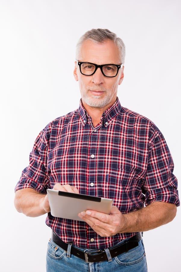 Homem cinzento confiável de idade com óculos segurando um comprimido fotos de stock royalty free