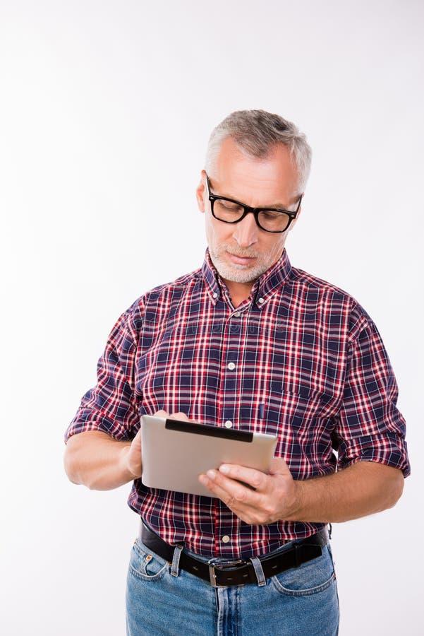 Homem cinzento confiável de idade com óculos a trabalhar com comprimido imagens de stock royalty free