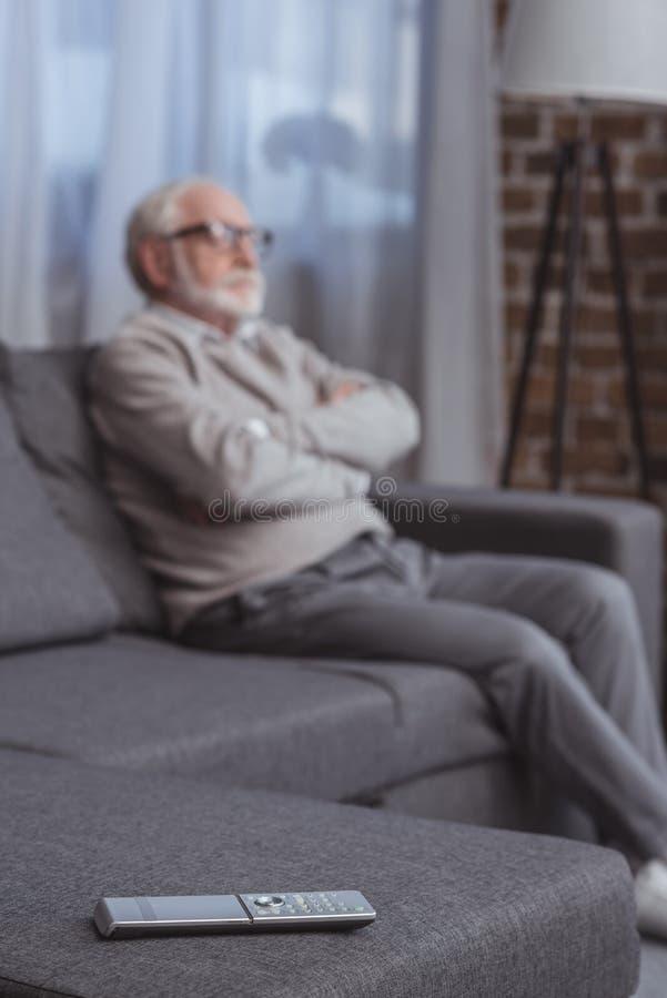 homem cinzento considerável do cabelo que senta-se no sofá com os braços cruzados com controlo a distância imagem de stock royalty free