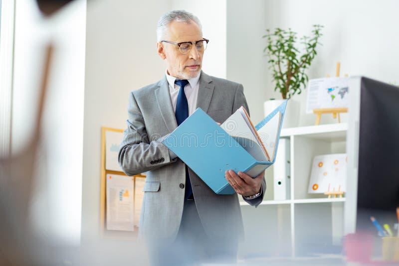 Homem cinzento-de cabelo calmo que lança através dos papéis na dobra espaçoso imagem de stock