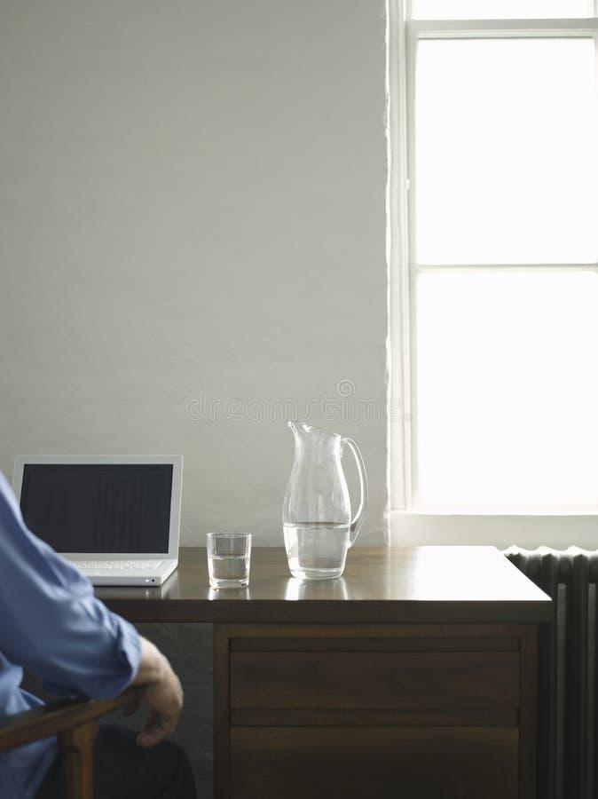 Homem colhido na mesa com portátil fotografia de stock royalty free