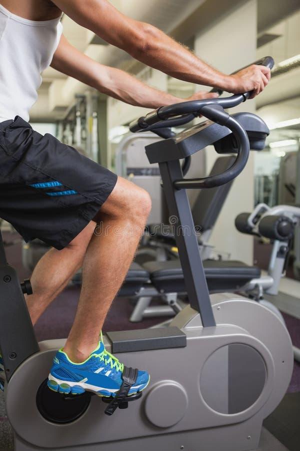 Homem colhido que dá certo na bicicleta de exercício no gym fotos de stock