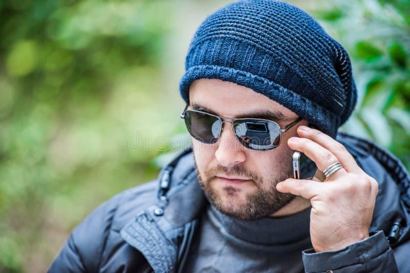 Homem com óculos de sol e um chapéu que falam no telefone imagem de stock royalty free