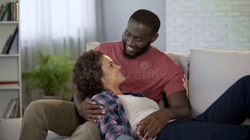 Homem com a afeição e a ternura que olham a esposa grávida, o amor e a ternura fotos de stock