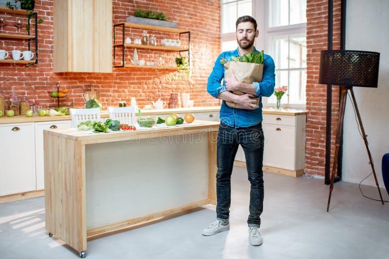 Homem com alimento saudável na cozinha fotografia de stock