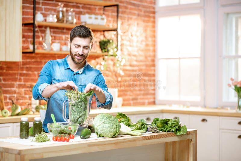 Homem com alimento saudável verde na cozinha foto de stock royalty free