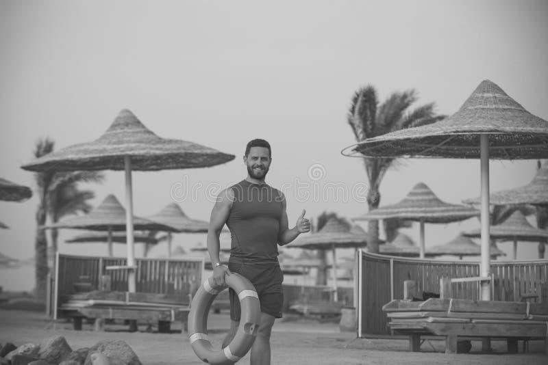 Homem com anel de vida vermelho na praia fotos de stock