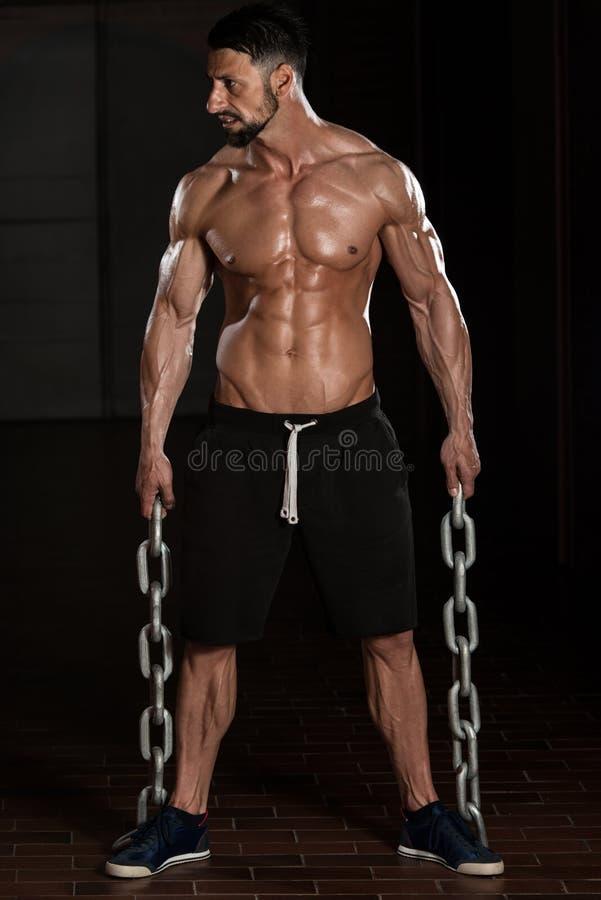Homem com as correntes que mostram seu corpo bem treinado fotos de stock