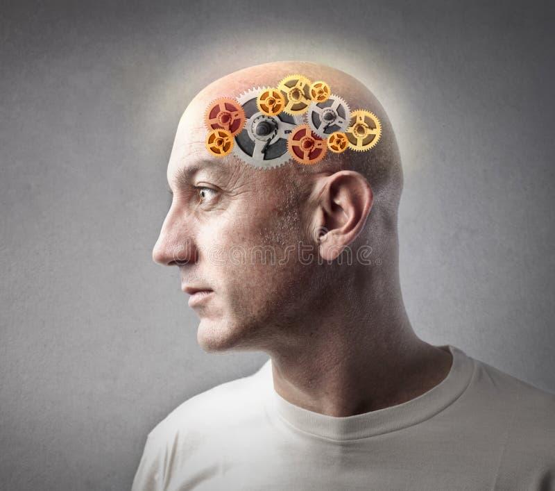 Homem com as engrenagens em seu cérebro imagens de stock royalty free