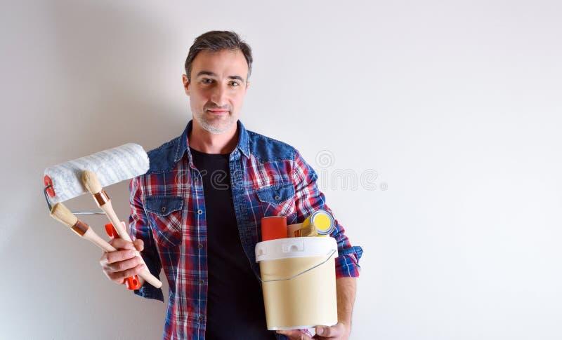 Homem com as ferramentas da pintura nas mãos e na parede branca atrás fotos de stock