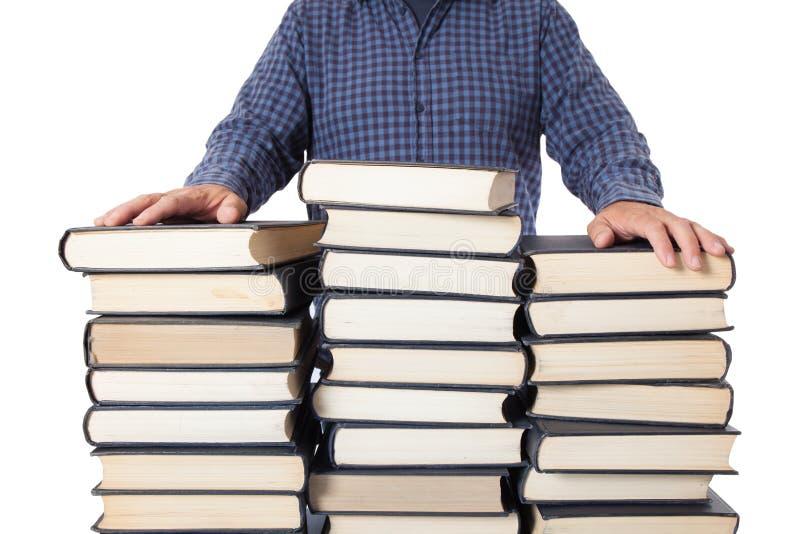Homem com as mãos postas sobre muitos livros imagens de stock