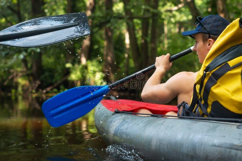 Homem com as pás na nadada do caiaque ao longo do rio do jaungle imagens de stock royalty free