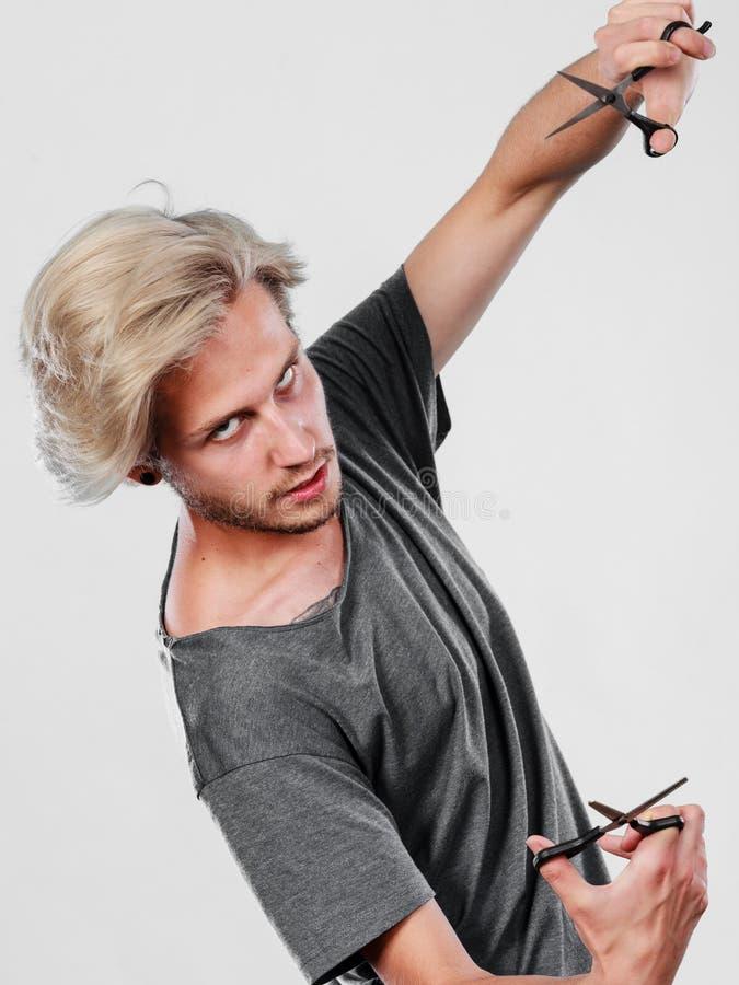 Homem com as tesouras para haircutting imagem de stock