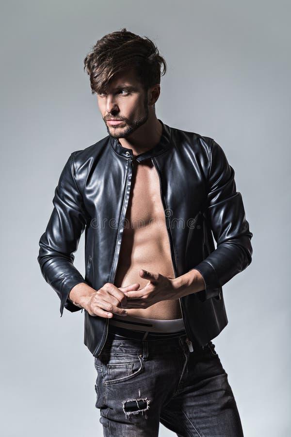 Homem com atitude no casaco de cabedal e nas calças de brim que olham com relação ao sid imagens de stock royalty free