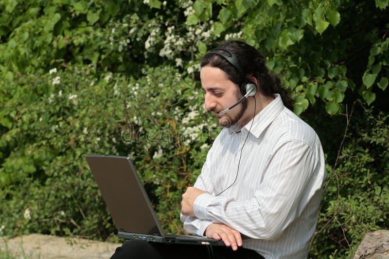 Homem com auriculares em uma árvore fotografia de stock royalty free