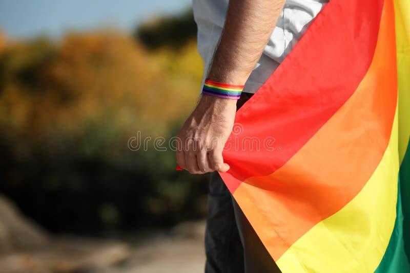 Homem com a bandeira como o ar livre alegre do símbolo, close up do arco-íris LGBT fotos de stock royalty free