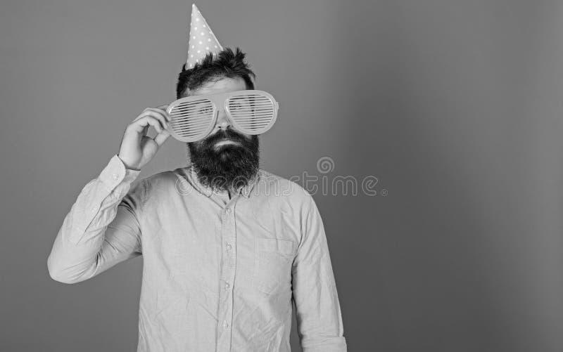 Homem com barba e bigode na cara calma s? em seu anivers?rio, fundo azul O indiv?duo no chap?u do partido comemora apenas fotografia de stock