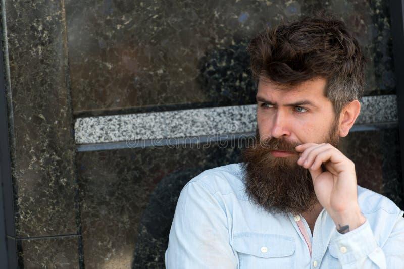 Homem com barba e bigode na cara concentrada, fundo de mármore preto O indivíduo olha interessado e curioso masculinity fotos de stock royalty free