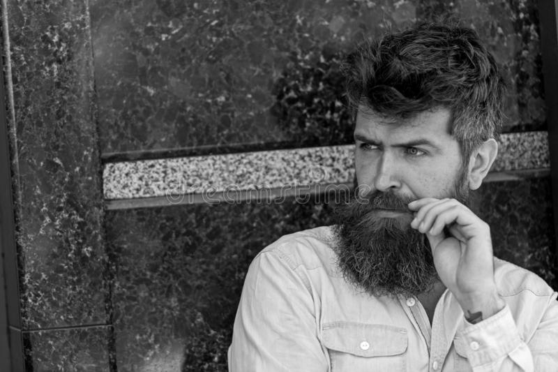 Homem com barba e bigode na cara concentrada, fundo de mármore preto O indivíduo olha interessado e curioso masculinity foto de stock