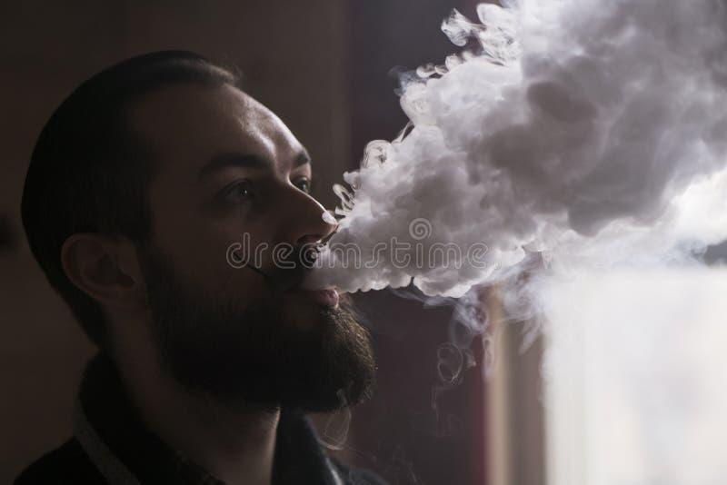 Homem com barba e Mustages Vaping um cigarro eletrônico Atomizador do fumo do moderno de Vaper e nuvem de fumo de Exhals fotografia de stock