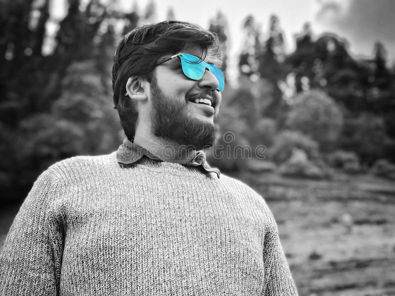 Homem com barba e os óculos de sol protegidos azul fotografia de stock