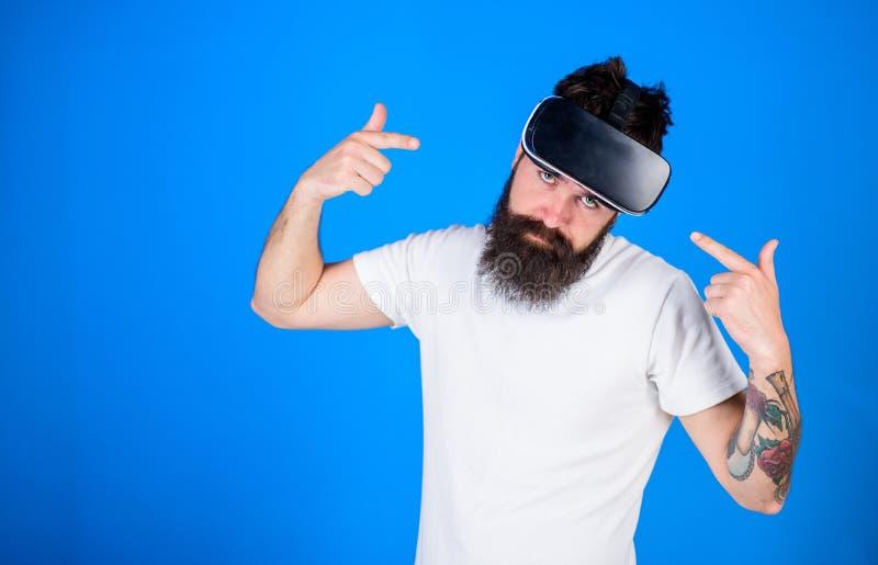 Homem com a barba na moda que anuncia o dispositivo novo no fundo azul Moderno com olhar fresco e a barba à moda que aponta em VR imagem de stock