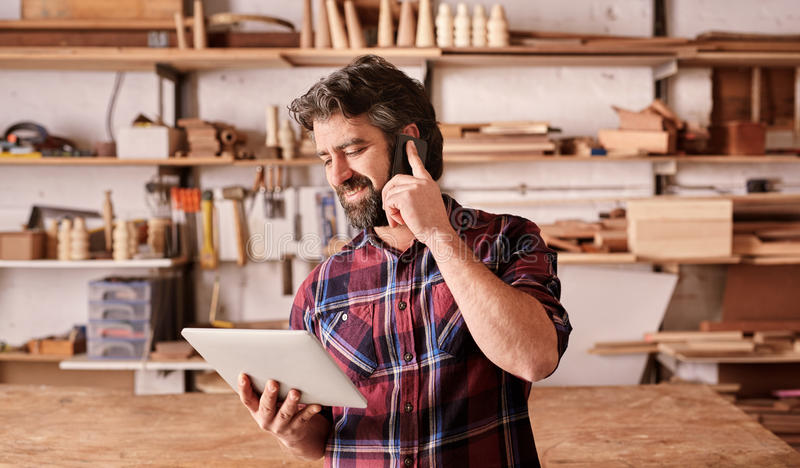 Homem com a barba no estúdio da carpintaria usando o telefone e a tabuleta imagens de stock