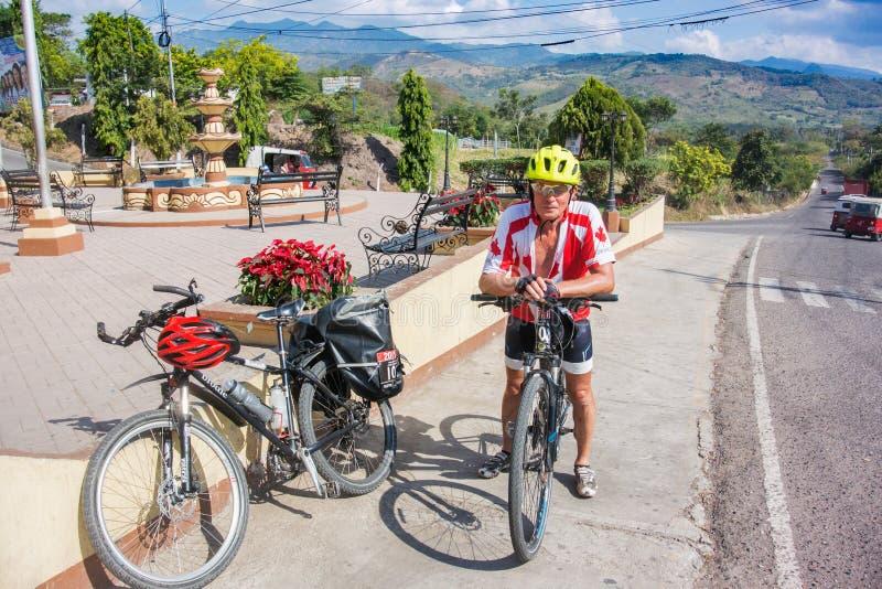 Homem, com a bicicleta na estrada na Guatemala foto de stock