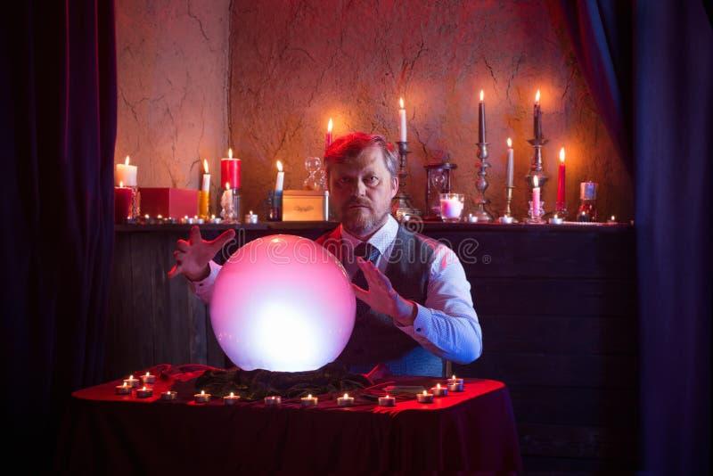 Homem com bola de cristal iluminada imagens de stock