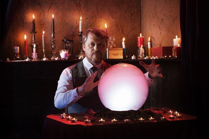 Homem com bola de cristal iluminada fotografia de stock royalty free