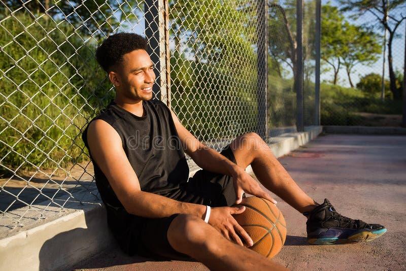 Homem com a bola no campo de básquete jogador que olha à câmera em um campo de básquete fotografia de stock royalty free