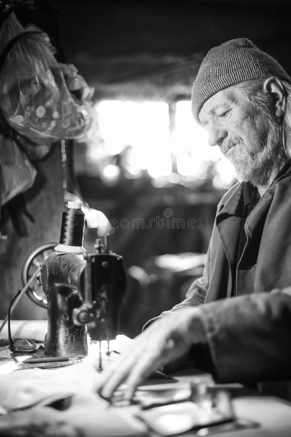 Homem com bw da máquina de costura fotos de stock royalty free