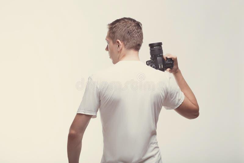 Homem com a câmera isolada no fundo claro Câmara digital da terra arrendada do homem novo Conceito do estilo de vida, do curso e  fotografia de stock