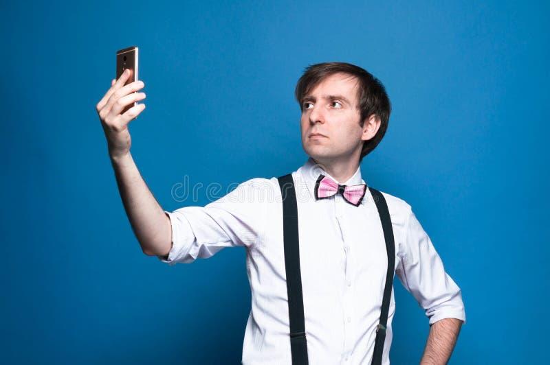 Homem com cabelo escuro em camisa cor-de-rosa com mangas enroladas, gravata-arco e espartilho preto tirando selfie sobre fundo az foto de stock