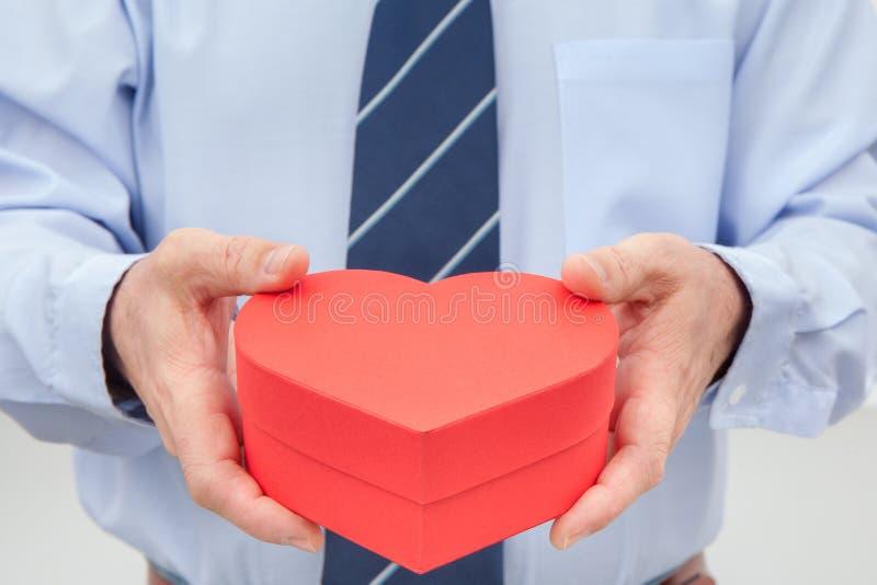 Homem com a caixa de presente vermelha fechado nas mãos imagem de stock royalty free