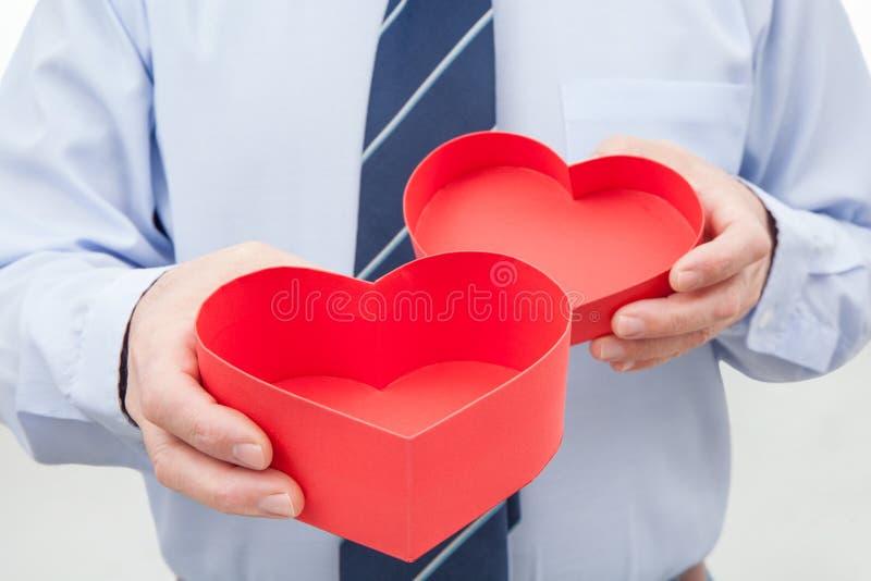 Homem com a caixa de presente vermelha nas mãos imagens de stock
