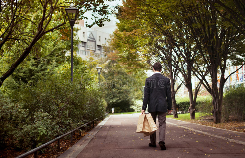 Homem com caminhadas dos sacos de compras apenas fotografia de stock
