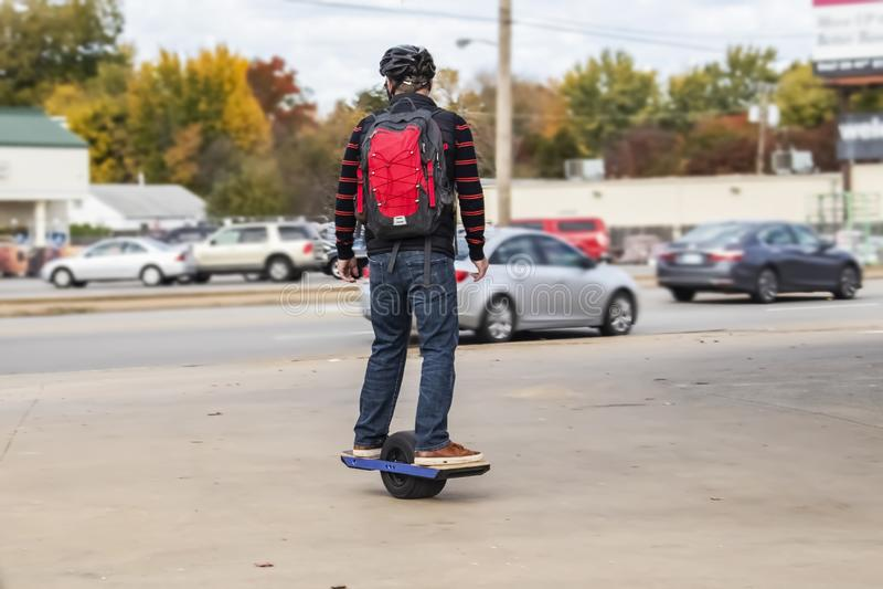 Homem com capacete e backback em um skate motorizado roda no passeio na área urbana com os carros no stree e as lojas e a queda foto de stock royalty free