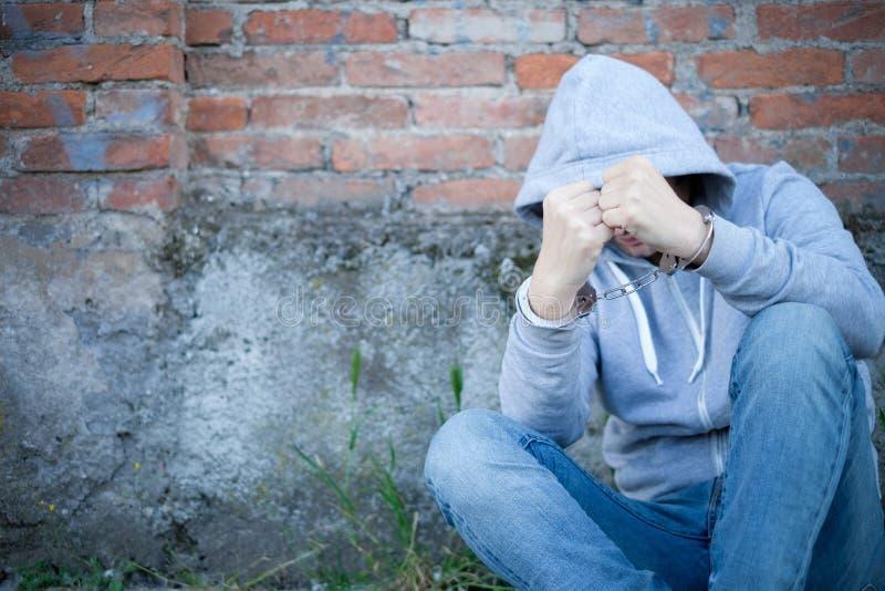 Homem com a cara escondida travada com algema imagens de stock