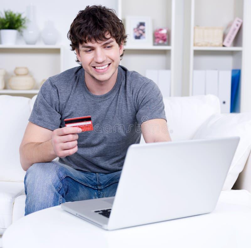 Homem com cartão e portátil de crédito