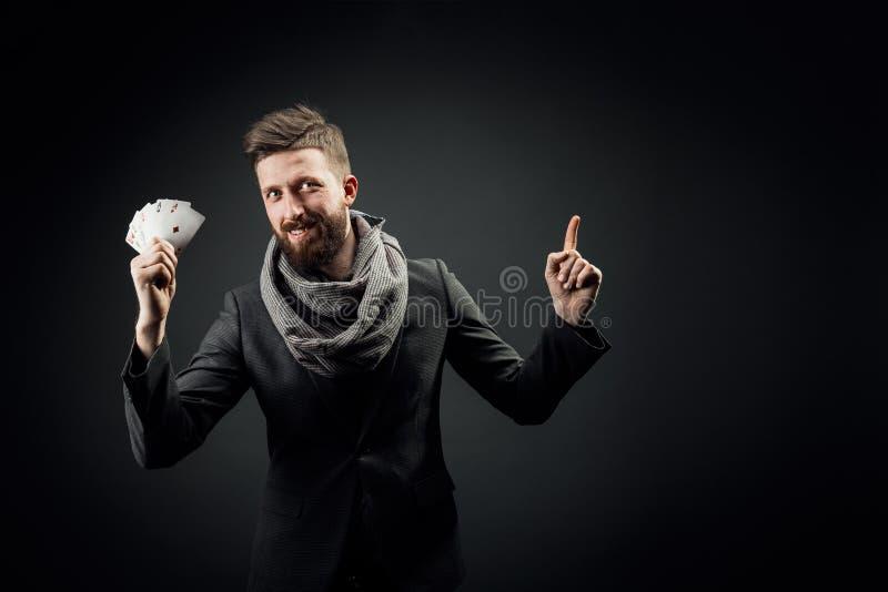 Homem com cartões de jogo em um fundo escuro fotografia de stock royalty free