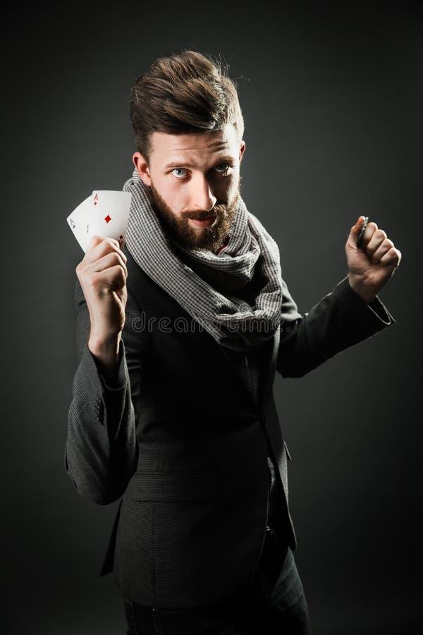 Homem com cartões de jogo em um fundo escuro imagem de stock royalty free
