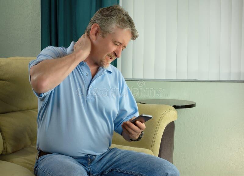 Homem com caso mau da síndrome do pescoço da tabuleta uma condição crônica da dor do apego da tecnologia usando o smartphone dema fotos de stock royalty free