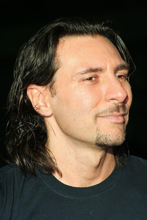 Homem com cavanhaque e cabelo longo no fundo preto fotografia de stock