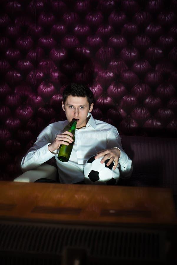 Homem com cerveja e bola do futebol que olham a tevê imagem de stock royalty free