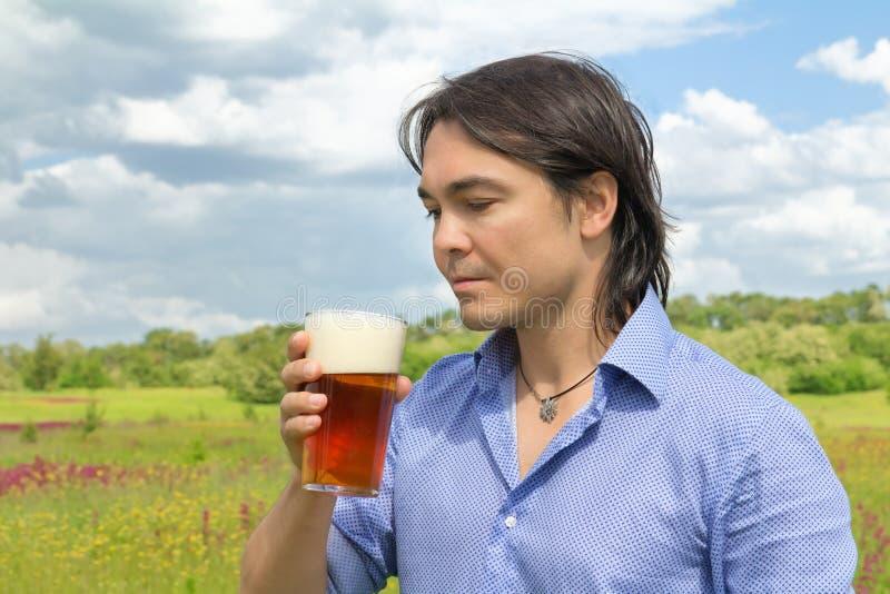 Homem com cerveja no prado da mola fotografia de stock royalty free