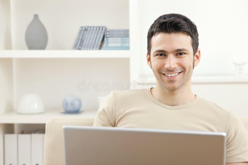 Homem com computador portátil em casa foto de stock royalty free