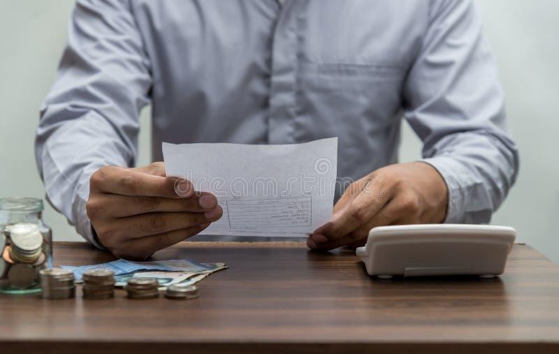 Homem com conta e pilha de moeda no vintage da tabela do escritório para negócios imagem de stock royalty free