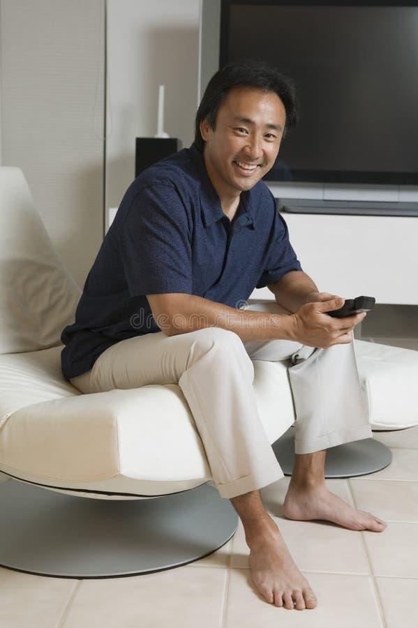 Homem com controlo a distância na tela da tevê de Front Of Large em casa fotografia de stock royalty free